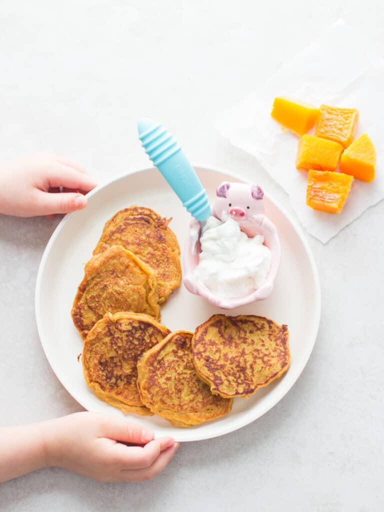5 butternut squash pancakes spread out on a plate with yogurt in a small bowl
