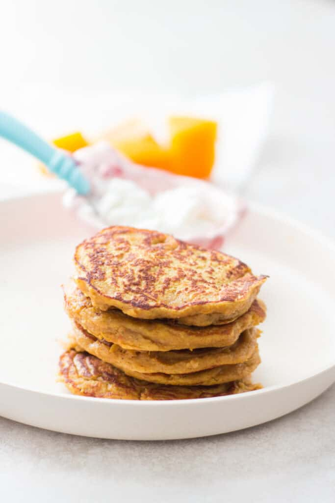 stacked pancakes with yogurt in the background