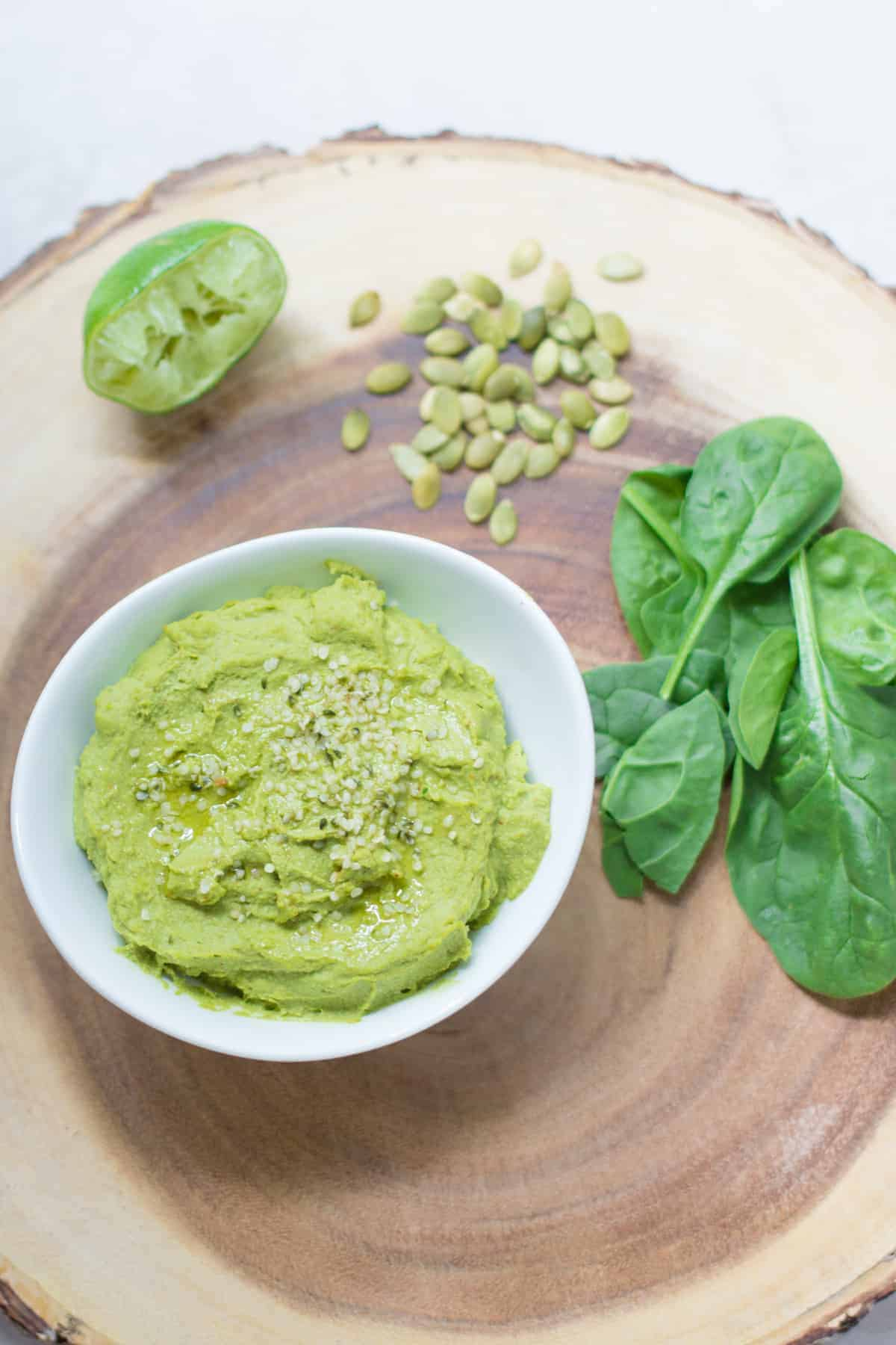 hummus in white bowl on wooden board along with pumpkin seeds, spinach, and lime