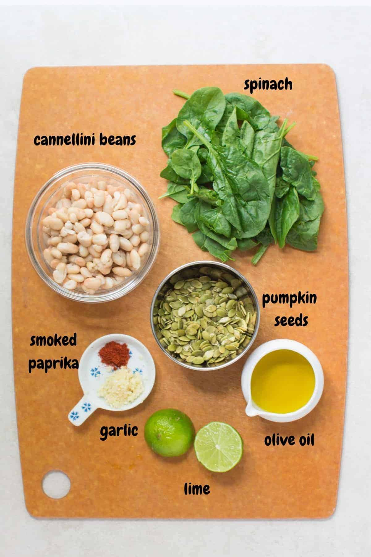 all the ingredients for the hummus placed on wooden board