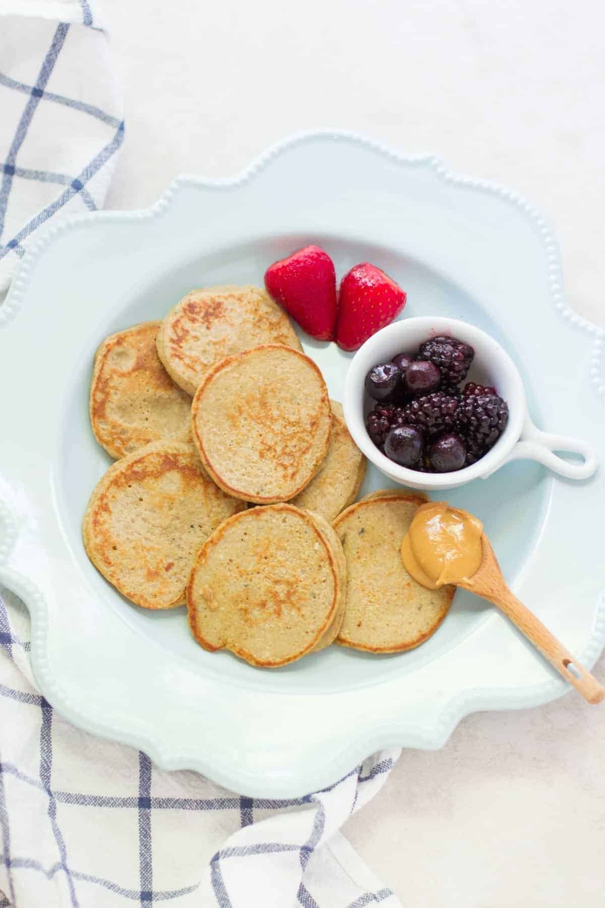 baby friendly banana protein pancakes spread out on a blue plate with berries and peanut butter