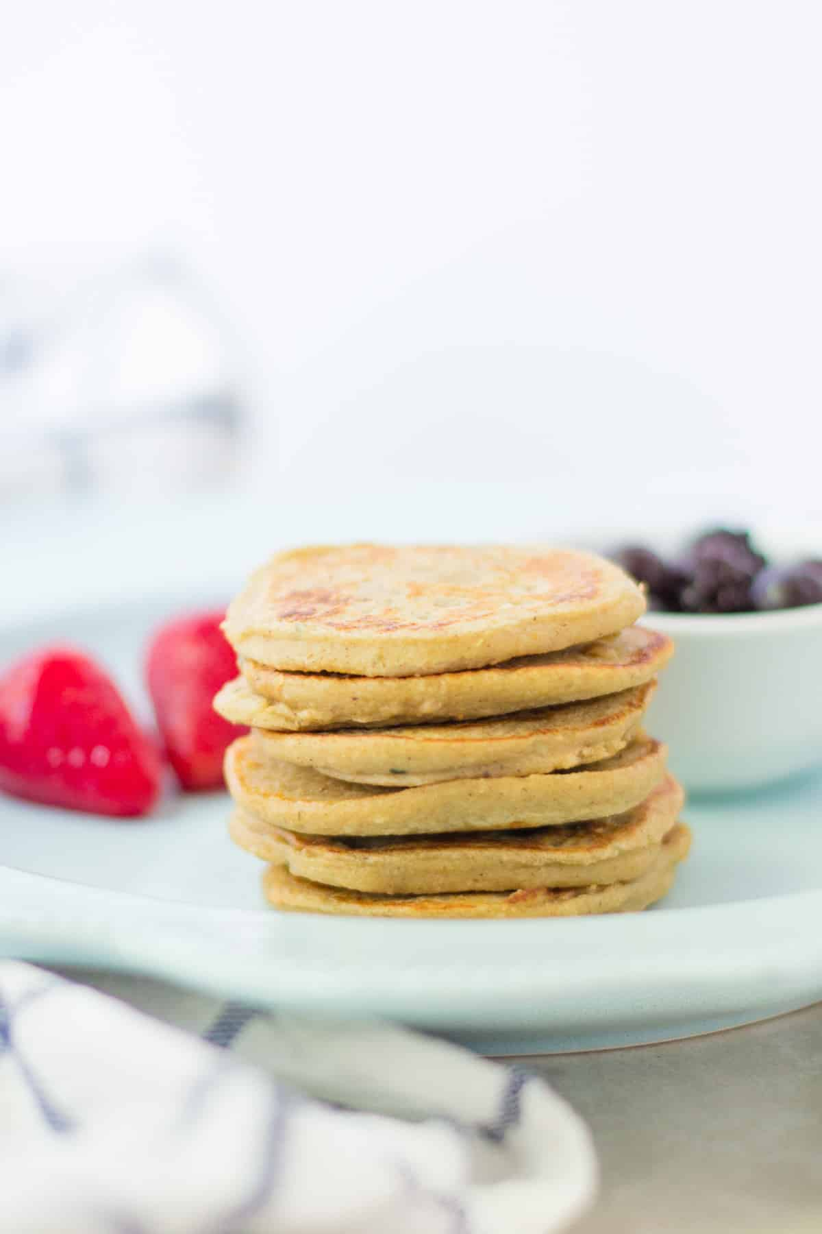a stack of baby pancakes with berries on the background
