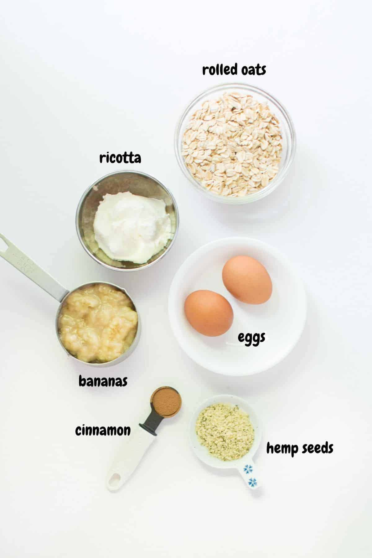 all the ingredients for the banana protein pancakes laid out on a white background