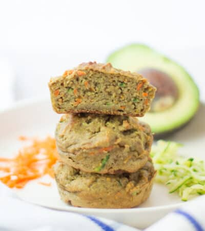 three stacked zucchini carrot avocado muffins with the very top one sliced in half to show the inside