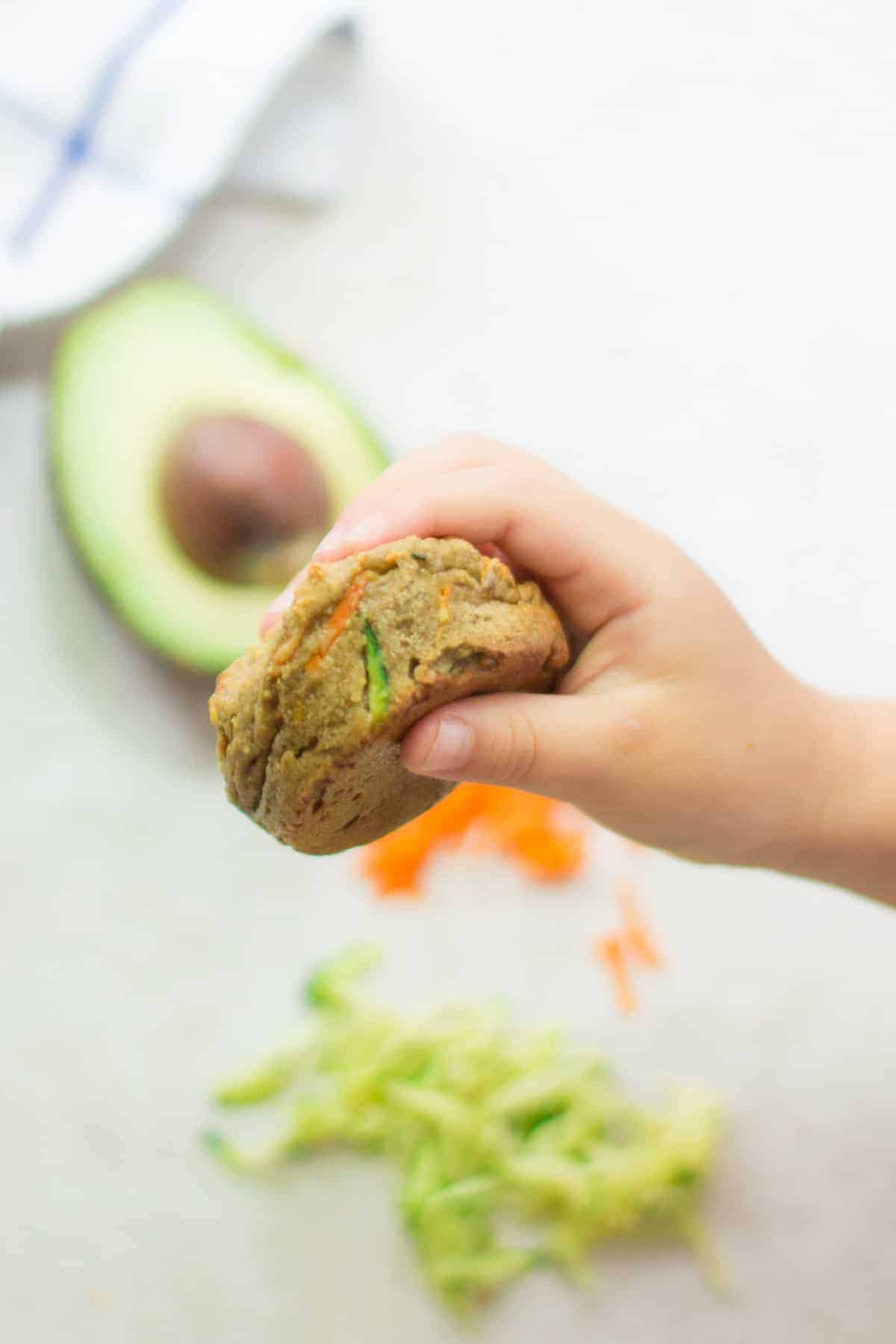 my toddler holding a zucchini carrot muffin with zucchini, carrots, and avocado in the background