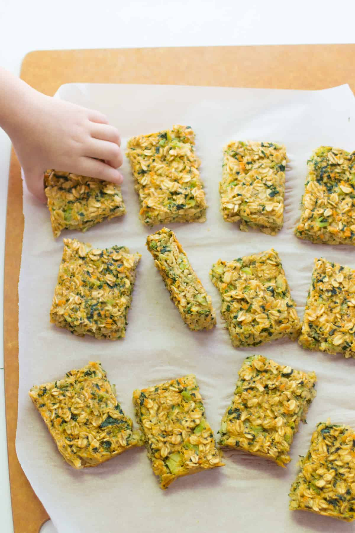 Sliced vegetable oats on a parchment paper with a toddler hand grabbing one piece