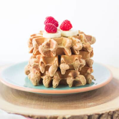 three stacked peanut butter waffles topped with banana and raspberries