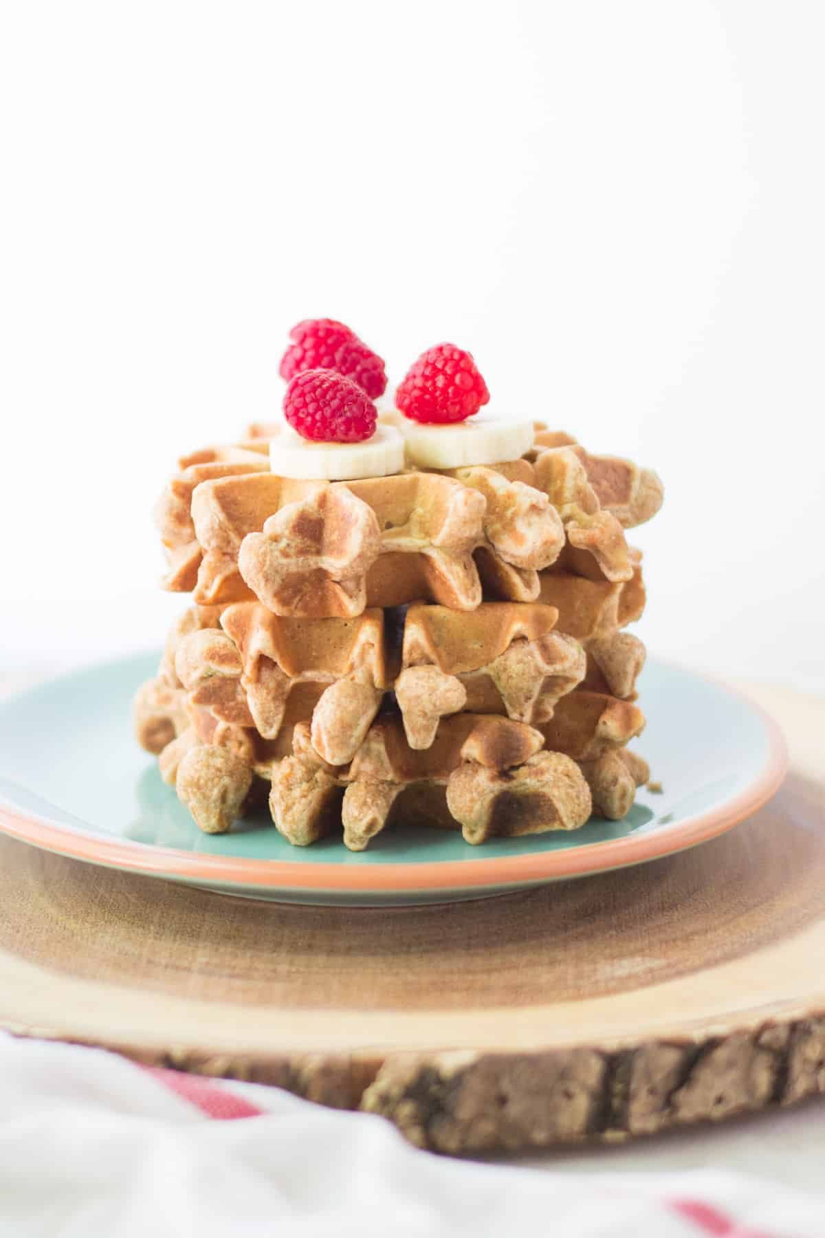 three stacked peanut butter vegetable waffles topped with banana and raspberries