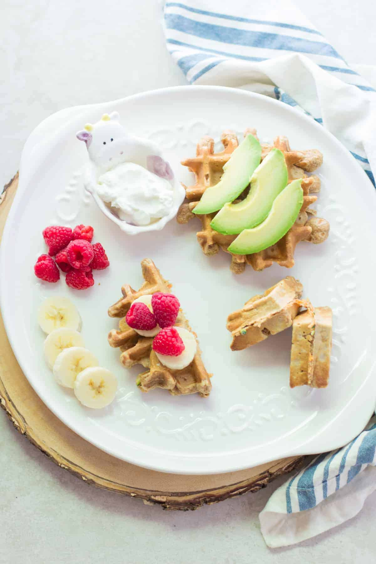 a waffle topped with avocado slices, waffle half with banana and raspberries and the other half folded to show thickness.