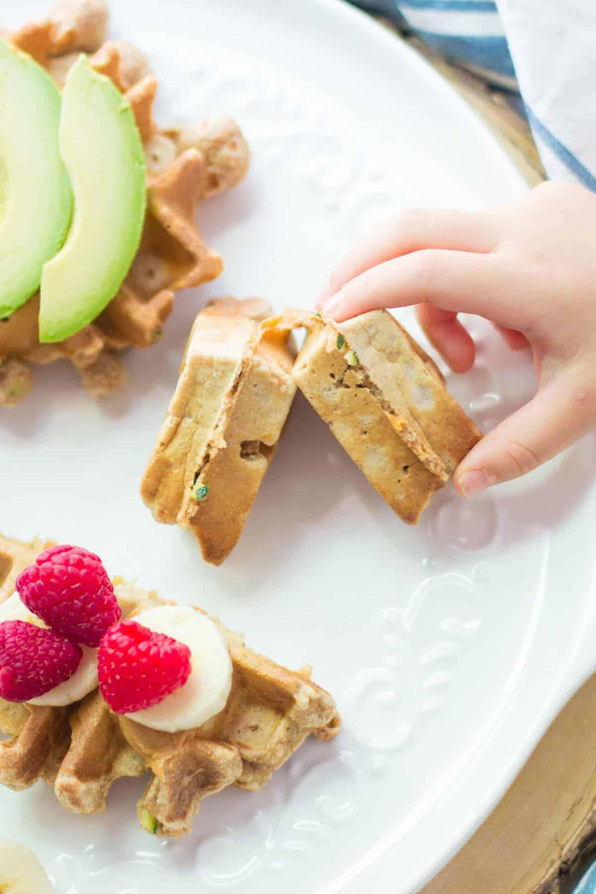 a toddler hand grabbing a waffle piece