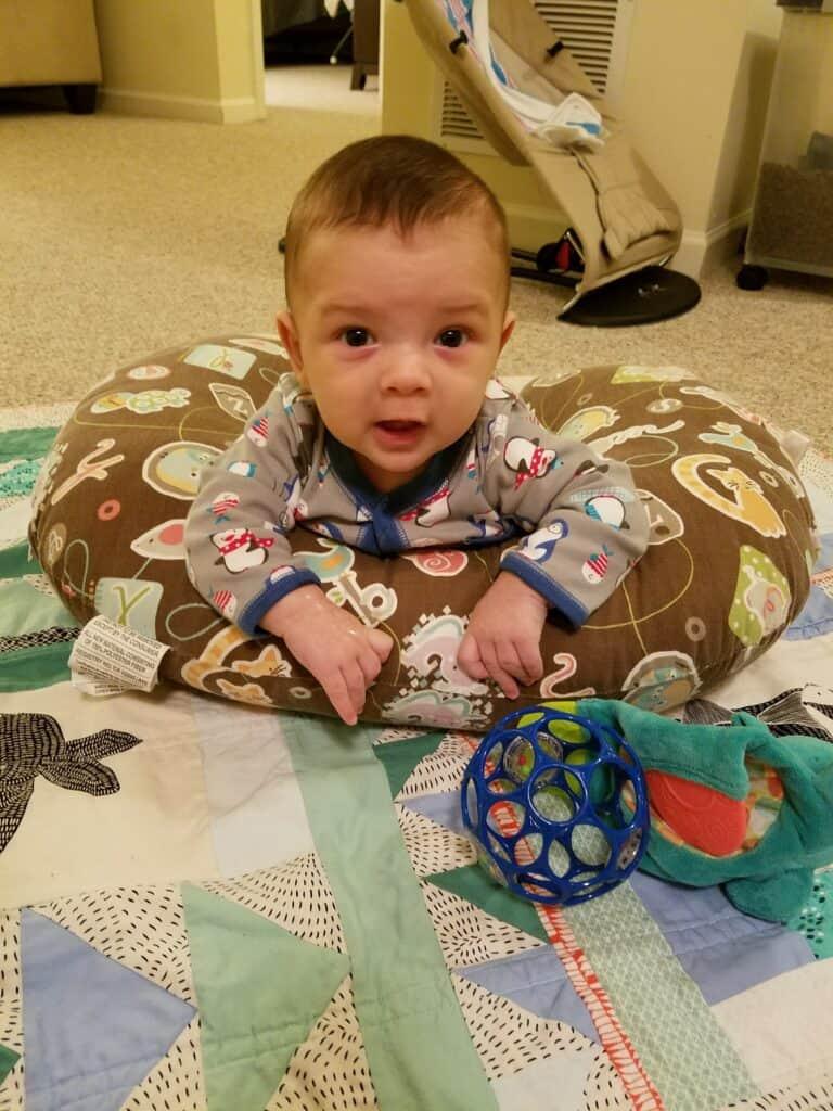 baby doing tummy time on boppy pillow