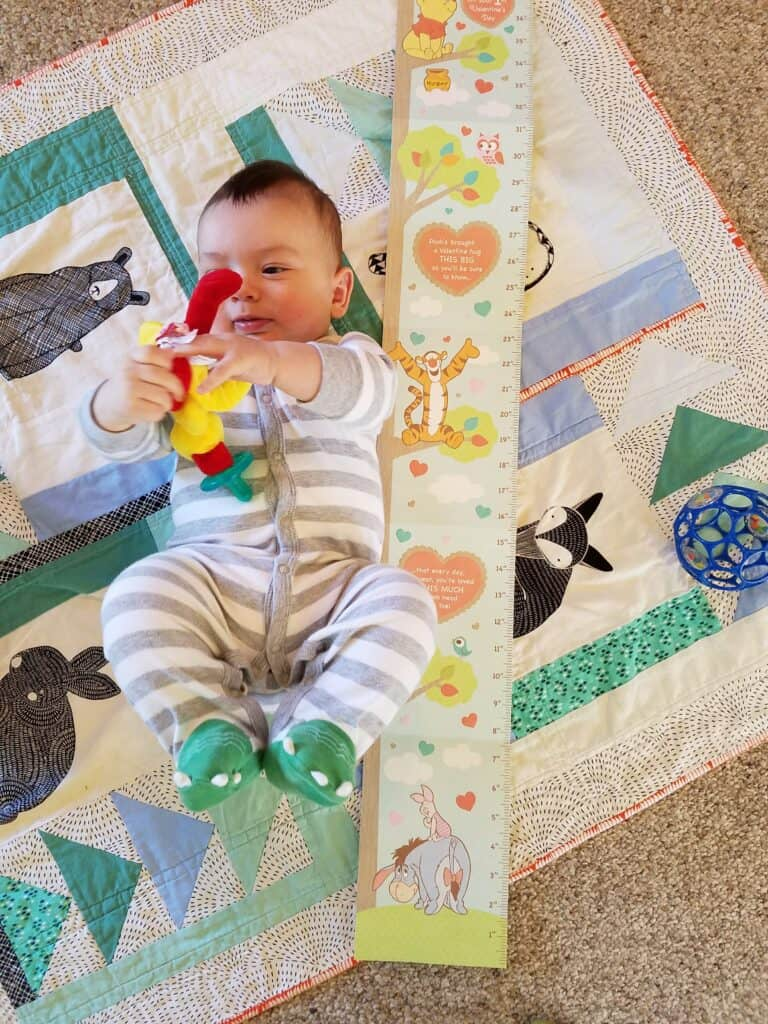 baby in a dinosaur zip up laying down with feet raised