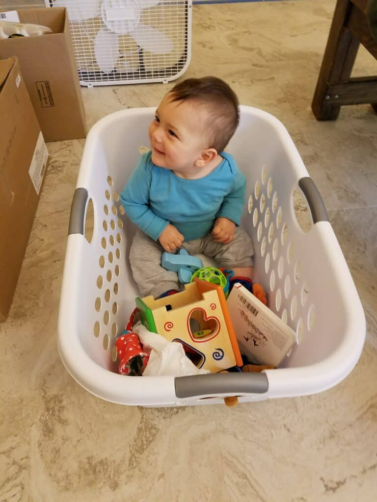 baby inside a laundry basket with toys