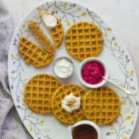healthy pumpkin baby waffles on a fall decorative plate with ricotta, maple syrup, and beet dip in separate bowls