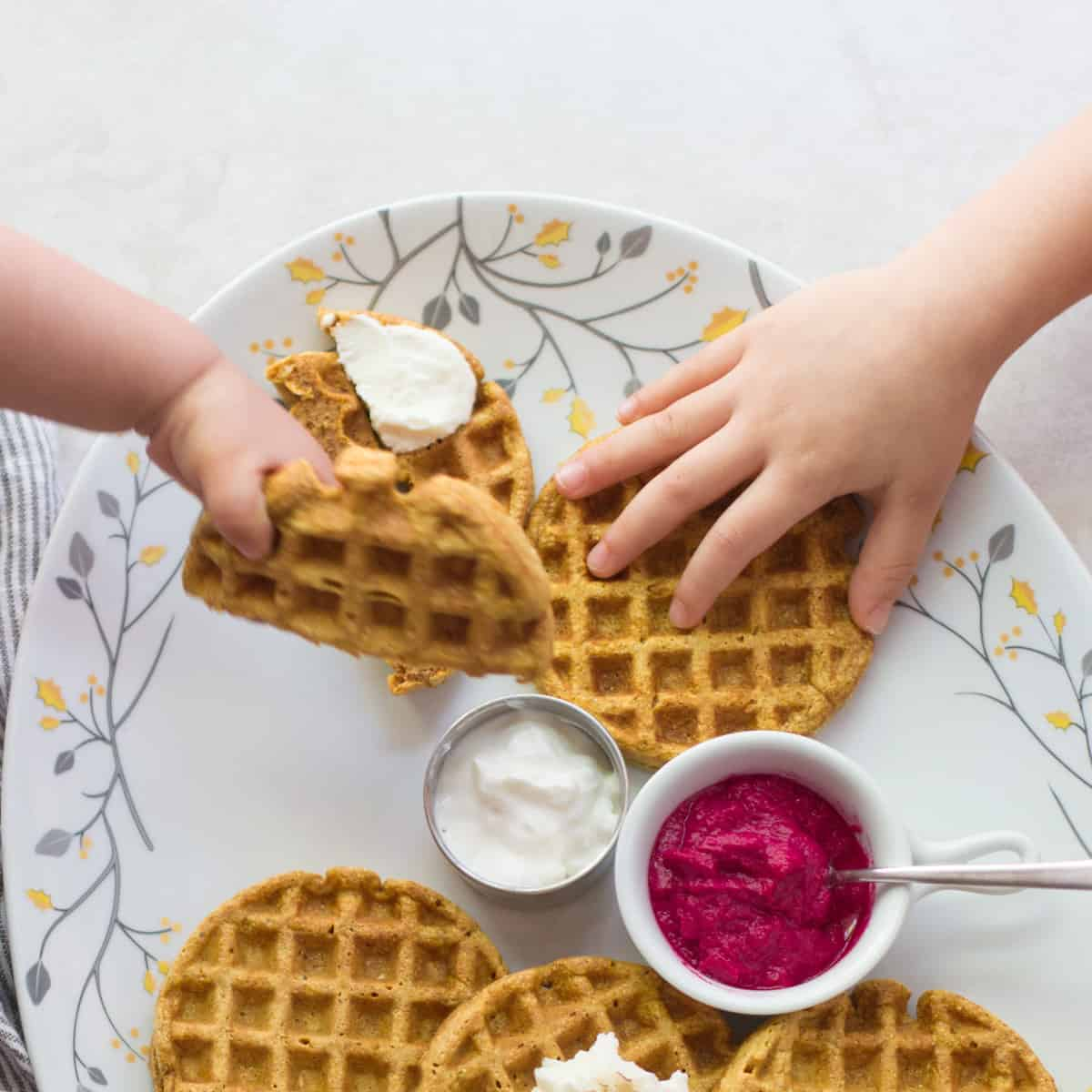a baby's hand grabbing the waffle in the air