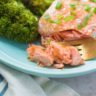 a close up shot of teriyaki glazed salmon flaked with a fork with broccoli on the side