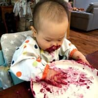 a picture of baby's hands and face covered in beet hummus