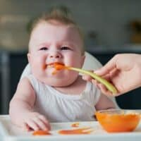 baby in high chair refusing to open mouth to mom holding a spoon with puree