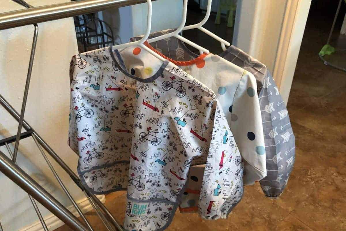 three full-sleeved bibs hung on laundry rack